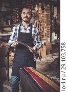 Купить «man worker displaying various belts in leather workshop», фото № 29103758, снято 19 октября 2018 г. (c) Яков Филимонов / Фотобанк Лори