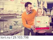 Купить «Father and daughter enjoying their purchase of canary bird in pet shop», фото № 29103798, снято 19 января 2017 г. (c) Яков Филимонов / Фотобанк Лори