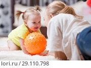 Купить «woman with her baby playing with a ball, while they are lying on plush carpet in the living room», фото № 29110798, снято 26 сентября 2018 г. (c) Оксана Кузьмина / Фотобанк Лори