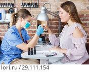 Купить «Professional manicurist in mask doing manicure by nail to girl», фото № 29111154, снято 30 мая 2018 г. (c) Яков Филимонов / Фотобанк Лори