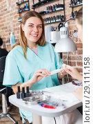 Купить «Manicurist filing and shaping nails to girl in modern beauty salon», фото № 29111158, снято 30 мая 2018 г. (c) Яков Филимонов / Фотобанк Лори