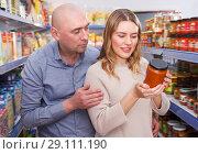 Купить «Adult family couple discussing in the food store», фото № 29111190, снято 11 апреля 2018 г. (c) Яков Филимонов / Фотобанк Лори