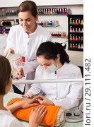 Купить «Manicurists performing manicure», фото № 29111482, снято 28 апреля 2017 г. (c) Яков Филимонов / Фотобанк Лори