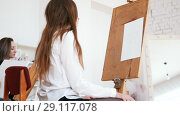 Young attractive woman sits behind the easel. Стоковое видео, видеограф Константин Шишкин / Фотобанк Лори
