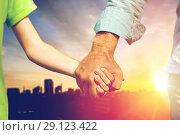Купить «close up of grandfather and grandson holding hands», фото № 29123422, снято 9 июля 2016 г. (c) Syda Productions / Фотобанк Лори