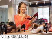 Купить «woman taking photo by smartphone at shoe store», фото № 29123458, снято 22 сентября 2017 г. (c) Syda Productions / Фотобанк Лори