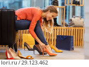 Купить «young woman trying high heeled shoes at store», фото № 29123462, снято 22 сентября 2017 г. (c) Syda Productions / Фотобанк Лори