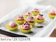 Купить «close up of frosted cupcakes or muffins on tray», фото № 29123678, снято 20 октября 2017 г. (c) Syda Productions / Фотобанк Лори