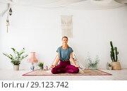 Купить «woman meditating in lotus pose at yoga studio», фото № 29123742, снято 21 июня 2018 г. (c) Syda Productions / Фотобанк Лори