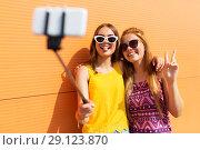 Купить «teenage girls taking picture by selfie stick», фото № 29123870, снято 19 июля 2018 г. (c) Syda Productions / Фотобанк Лори