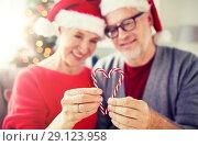 Купить «senior couple with heart of christmas candy canes», фото № 29123958, снято 14 сентября 2017 г. (c) Syda Productions / Фотобанк Лори