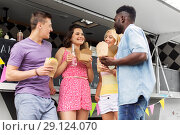 Купить «happy friends with drinks eating at food truck», фото № 29124070, снято 1 августа 2017 г. (c) Syda Productions / Фотобанк Лори