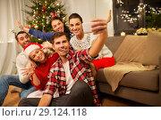 Купить «friends celebrating christmas and taking selfie», фото № 29124118, снято 17 декабря 2017 г. (c) Syda Productions / Фотобанк Лори