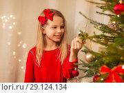 Купить «happy girl in red decorating christmas tree», фото № 29124134, снято 22 декабря 2017 г. (c) Syda Productions / Фотобанк Лори