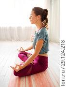 Купить «woman meditating in lotus pose at yoga studio», фото № 29124218, снято 21 июня 2018 г. (c) Syda Productions / Фотобанк Лори