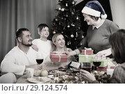 Купить «Elderly woman giving Christmas presents to family», фото № 29124574, снято 17 декабря 2017 г. (c) Яков Филимонов / Фотобанк Лори