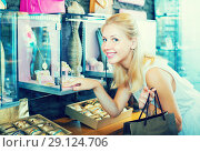 Купить «Smiling young woman customer looking fashion jewellery», фото № 29124706, снято 26 марта 2019 г. (c) Яков Филимонов / Фотобанк Лори