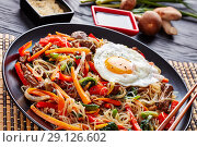 Купить «Japchae korean dish in a black plate, close up», фото № 29126602, снято 29 августа 2018 г. (c) Oksana Zh / Фотобанк Лори