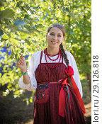 Купить «Smiling young woman in russian folk costume on the foliage background», фото № 29126818, снято 19 августа 2018 г. (c) Константин Шишкин / Фотобанк Лори
