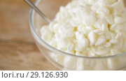 Купить «close up of cottage cheese in bowl on wooden table», видеоролик № 29126930, снято 21 августа 2018 г. (c) Syda Productions / Фотобанк Лори