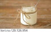yogurt or sour cream in glass jar on wooden table. Стоковое видео, видеограф Syda Productions / Фотобанк Лори