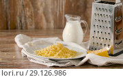 close up of grated cheese and jug of milk on table. Стоковое видео, видеограф Syda Productions / Фотобанк Лори