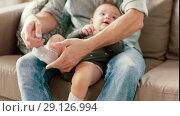 Купить «father putting sock on baby daughters foot», видеоролик № 29126994, снято 17 сентября 2018 г. (c) Syda Productions / Фотобанк Лори