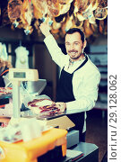 Купить «Smiling man seller weighing on scales piece of meat», фото № 29128062, снято 2 января 2017 г. (c) Яков Филимонов / Фотобанк Лори