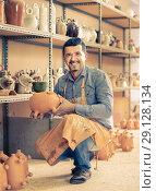 Купить «cheerful man potter holding ceramic vessels», фото № 29128134, снято 20 октября 2018 г. (c) Яков Филимонов / Фотобанк Лори