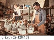 Купить «Workers in ceramics workroom with pottery wheel», фото № 29128138, снято 22 октября 2018 г. (c) Яков Филимонов / Фотобанк Лори