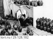Купить «woman potter holding black glazed ceramics vessels in studio», фото № 29128182, снято 6 декабря 2019 г. (c) Яков Филимонов / Фотобанк Лори