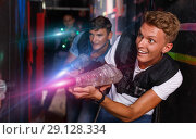 Купить «Young guy holding colored laser guns and took aim during laser t», фото № 29128334, снято 23 августа 2018 г. (c) Яков Филимонов / Фотобанк Лори