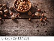 Купить «Mixed nuts on old wooden background», фото № 29137258, снято 21 ноября 2016 г. (c) Майя Крученкова / Фотобанк Лори