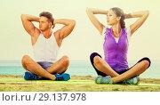 Купить «Woman and man sitting cross-legged do yoga poses on beach», фото № 29137978, снято 22 октября 2018 г. (c) Яков Филимонов / Фотобанк Лори