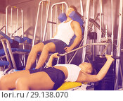 Купить «Young well trained woman lying on back on bench and lifting weights in shoulder press machinery», фото № 29138070, снято 20 октября 2018 г. (c) Яков Филимонов / Фотобанк Лори