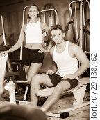 Купить «satisfied young man and woman taking pause between exercising in gym», фото № 29138162, снято 4 октября 2016 г. (c) Яков Филимонов / Фотобанк Лори