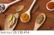 Купить «spoons with different spices on wooden table», видеоролик № 29138414, снято 20 сентября 2018 г. (c) Syda Productions / Фотобанк Лори