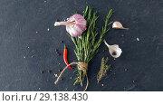 Купить «rosemary, garlic and chili pepper on stone surface», видеоролик № 29138430, снято 20 сентября 2018 г. (c) Syda Productions / Фотобанк Лори