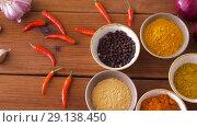 Купить «bowls with different spices on wooden table», видеоролик № 29138450, снято 20 сентября 2018 г. (c) Syda Productions / Фотобанк Лори