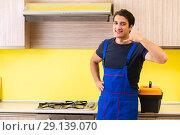 Купить «The young service contractor assembling kitchen furniture», фото № 29139070, снято 19 июня 2018 г. (c) Elnur / Фотобанк Лори