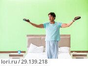 Купить «The young man in pajamas doing morning exercises», фото № 29139218, снято 21 июня 2018 г. (c) Elnur / Фотобанк Лори