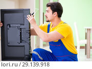 Купить «The male professional serviceman repairing tv at home», фото № 29139918, снято 8 мая 2018 г. (c) Elnur / Фотобанк Лори