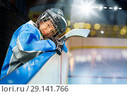 Teenage hockey player leans on the boards of rink. Стоковое фото, фотограф Сергей Новиков / Фотобанк Лори