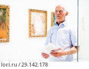 Купить «Man visiting painting exhibition», фото № 29142178, снято 9 июня 2018 г. (c) Яков Филимонов / Фотобанк Лори