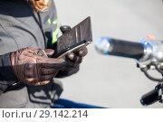 Купить «Смартфон в руках мотоциклиста, кожаные перчатки, крупный план», фото № 29142214, снято 15 сентября 2018 г. (c) Кекяляйнен Андрей / Фотобанк Лори