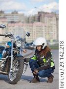 Купить «Девушка мотоциклистка проверяет и осматривает переднее колесо мотоцикла», фото № 29142218, снято 15 сентября 2018 г. (c) Кекяляйнен Андрей / Фотобанк Лори