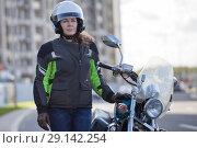 Купить «Женщина мотоциклистка стоит рядом с мотоциклом в городе», фото № 29142254, снято 15 сентября 2018 г. (c) Кекяляйнен Андрей / Фотобанк Лори