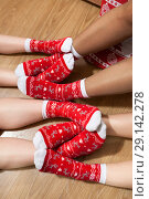 Human legs crossing on the floor with colorful Cristmas socks with red and white ornament. Стоковое фото, фотограф Кекяляйнен Андрей / Фотобанк Лори
