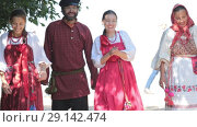 Купить «Group of men and women walking in russian folk costumes in nature. Smiling. Celebration», видеоролик № 29142474, снято 7 августа 2020 г. (c) Константин Шишкин / Фотобанк Лори