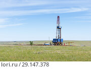 Купить «Drilling tower in the steppe. Steppe landscape with drilling rigs and equipment», фото № 29147378, снято 16 июня 2018 г. (c) Вадим Орлов / Фотобанк Лори